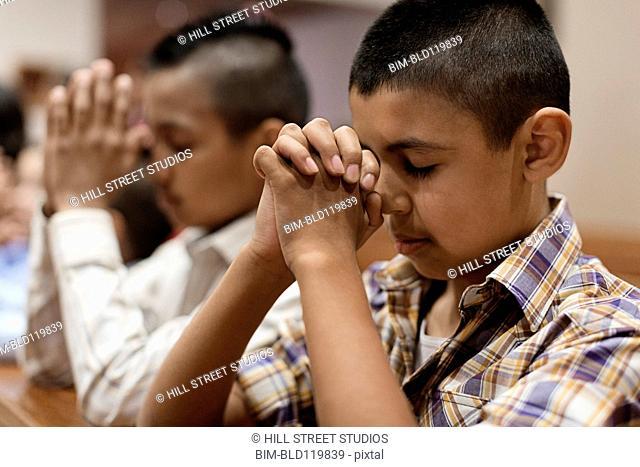 Hispanic boys praying in church