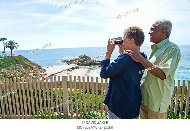 Senior couple outdoors, woman looking through binoculars, looking at view