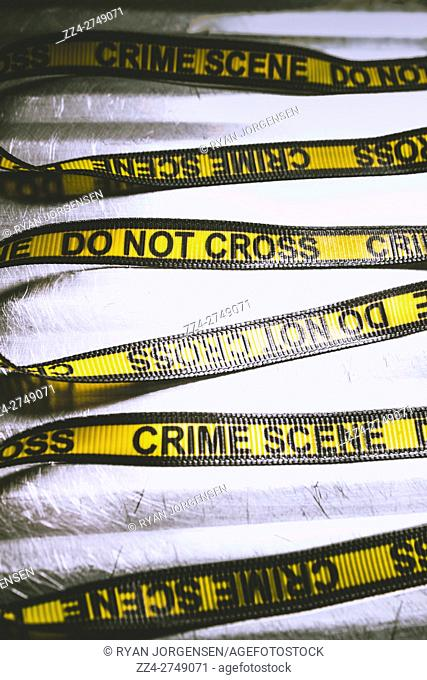 CSI still life on a yellow and black crime scene tape laying unwoven on forensic science bench. Unwrapping a murder investigation