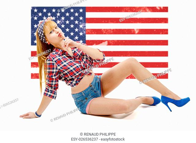 a pinup girl sitting on the floor with a US flag in the background