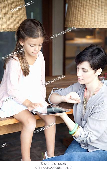 Mother and young daughter using digital tablet together