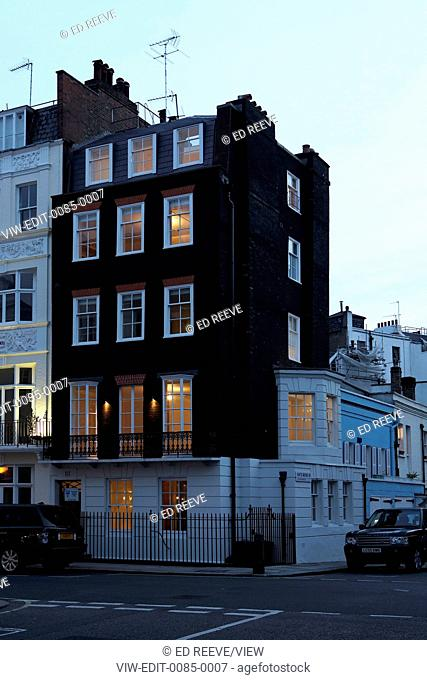Chesterfield Hill Apartment, London, United Kingdom. Architect: Work Ltd, 2014. Elevation of end-of-terrace facade at dusk