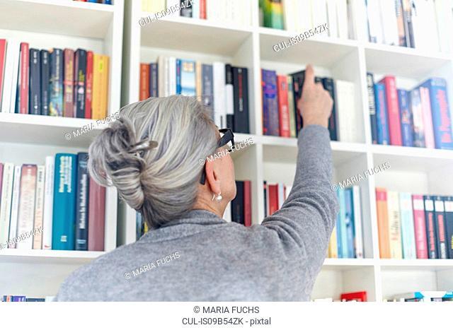 Senior woman taking book from bookshelf, rear view