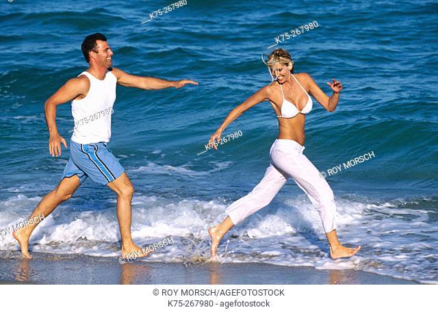 Man chasing his girlfriend on the beach