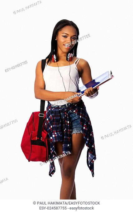 Beautiful happy student standing with binders and bag, on white
