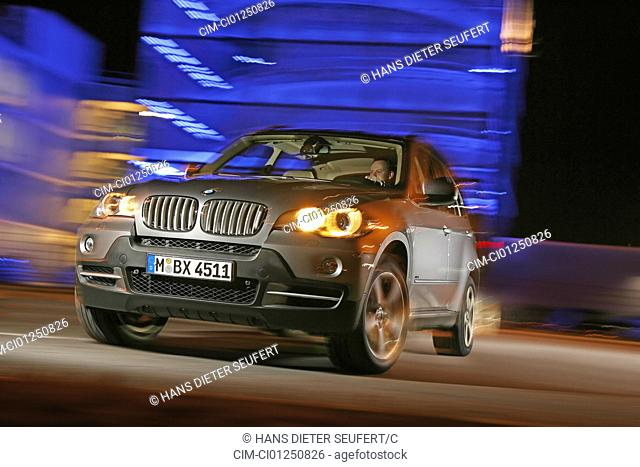 BMW X5 4.8i, model year 2006-, silver, driving, diagonal from the front, frontal view, City, verwischt, night shot, Evening admission