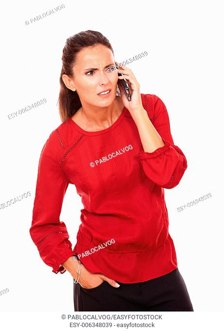 Portrait of confused hispanic lady on red blouse talking on her phone while looking to her left and standing on isolated white background - copyspace