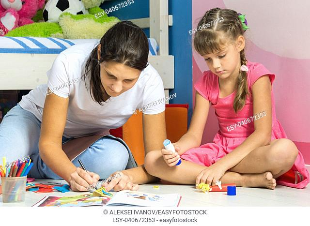 Mom and daughter sitting on the floor in the nursery and crafting crafts