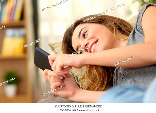 Portrait of a happy teenager reading a text in a smart phone on line lying on a couch in the living room at home