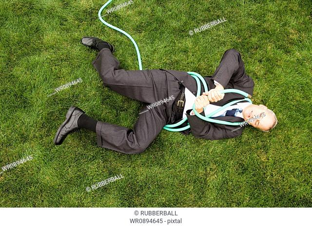 High angle view of a businessman playing with a hose