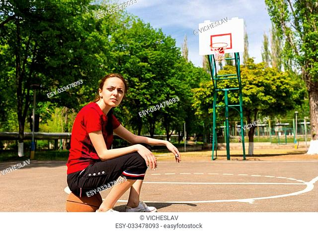 Full Length of Young Woman Sitting on Top of Basketball on Court in Lush Green Park with Backboard and Basket in Background