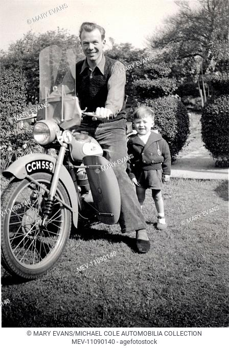 Man on a 1951/2 BSA Bantam D1 motorcycle in the garden with his son circa 1952