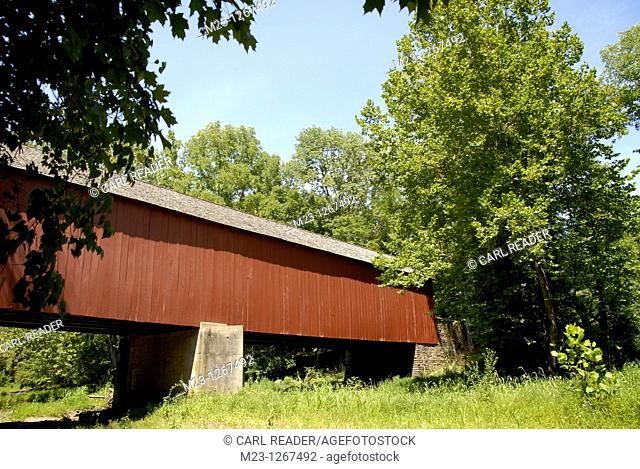 A red covered bridge is surrounded by deep green foliage, Pennsylvania, USA