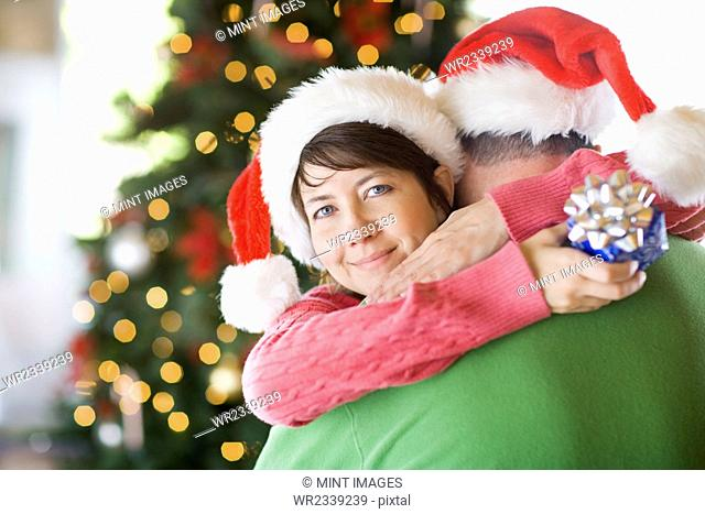 A couple wearing Santa hats hugging in front of a Christmas tree