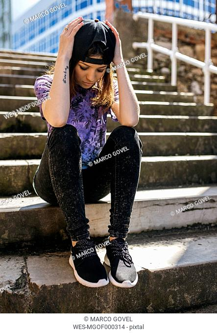 Young woman with baseball cap and tattoo sitting on staircase