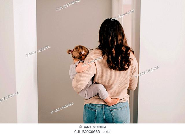 Mother carrying baby daughter through hall doorway, rear view