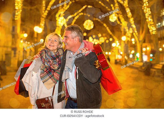 Mature couple xmas shopping on tree lined avenue, Majorca, Spain