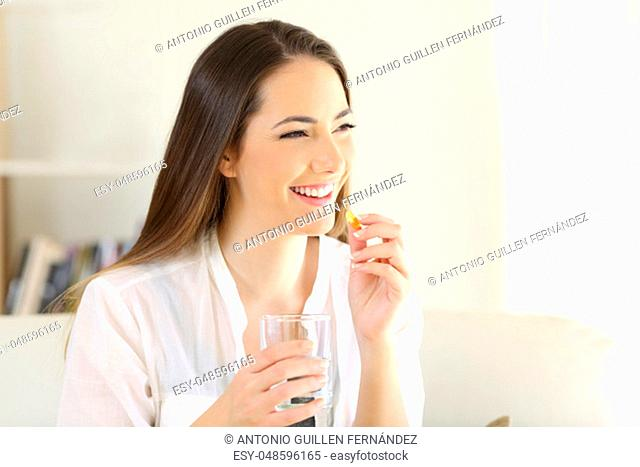 Happy woman taking a vitamin yellow pill sitting on a couch in the living room at home