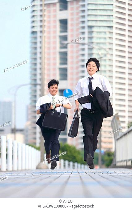 Young Japanese businessmen running on the street