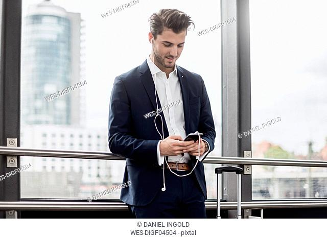 Young businessman at the window with cell phone, earbuds and rolling suitcase