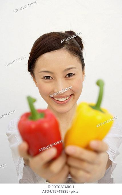View of a young woman holding bell peppers in her hands