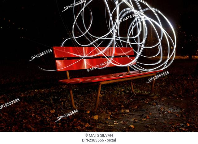 A red park bench in autumn with swirls of white light in the sky around it; Locarno, Ticino, Switzerland