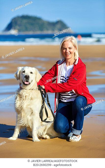Senior woman 60-70, Walking with dog on the beach, background Getaria, Zarautz, Gipuzkoa, Basque Country, Spain, Europe