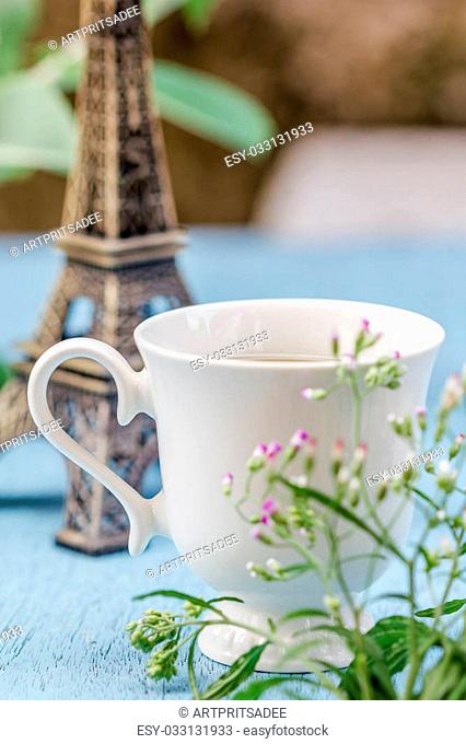 Image of morning tea cup decorated with small eiffel tower and fresh grass flower