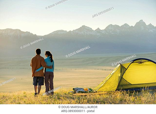 A young couple enjoy the last rays of the day while camping