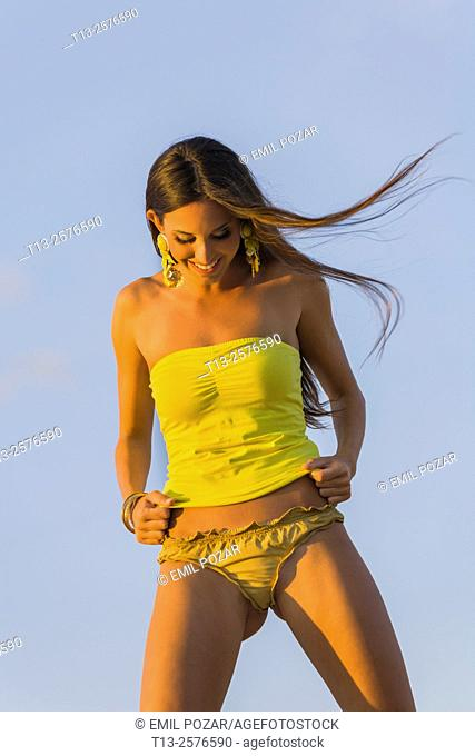 Fanciful young woman in swimsuit is laughing looking down at panties