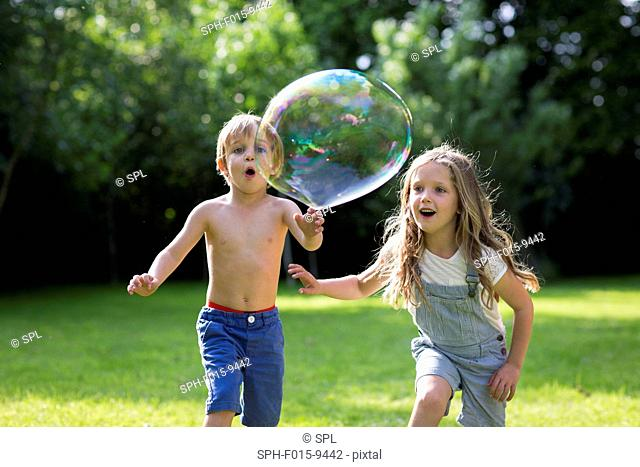 MODEL RELEASED. Brother and sister chasing bubbles in garden