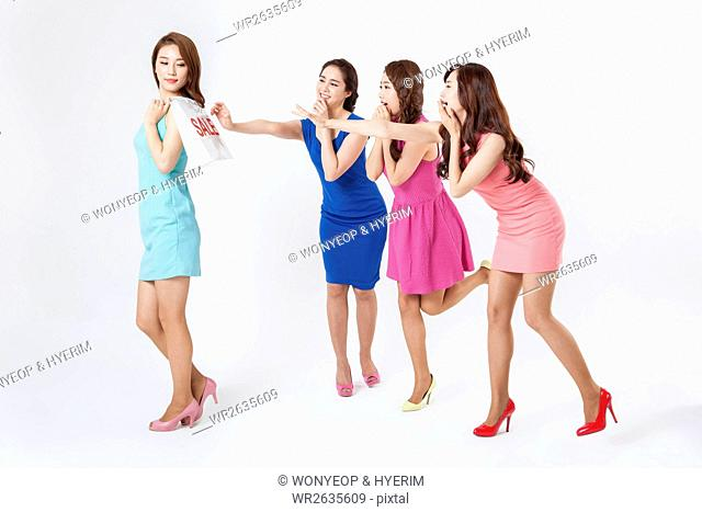 Young woman with shopping bag walking and three young women standing holding out hands for her