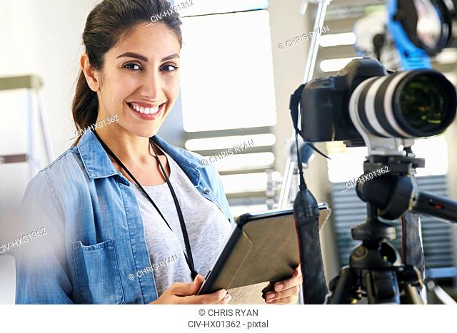 Portrait smiling female photographer using digital tablet behind camera in studio
