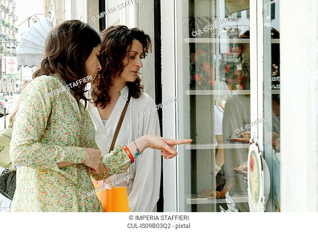 Two women pointing and looking at shop window, Milan, Italy