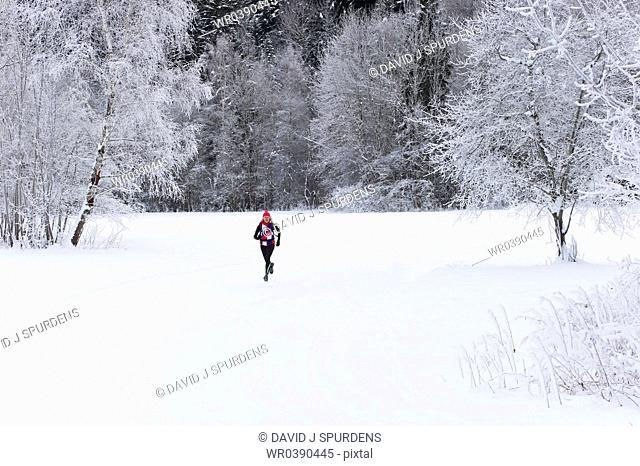 A jogger running through a snowy landscape