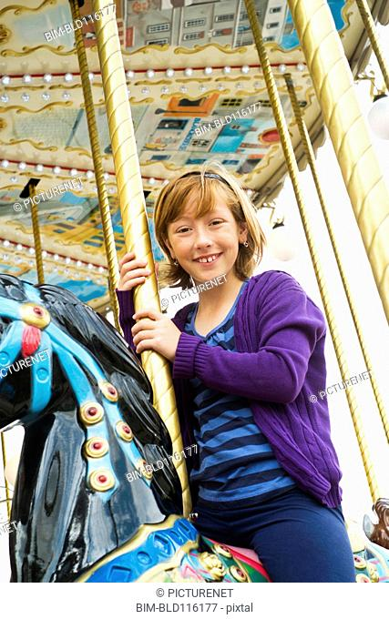 Caucasian girl riding carousel