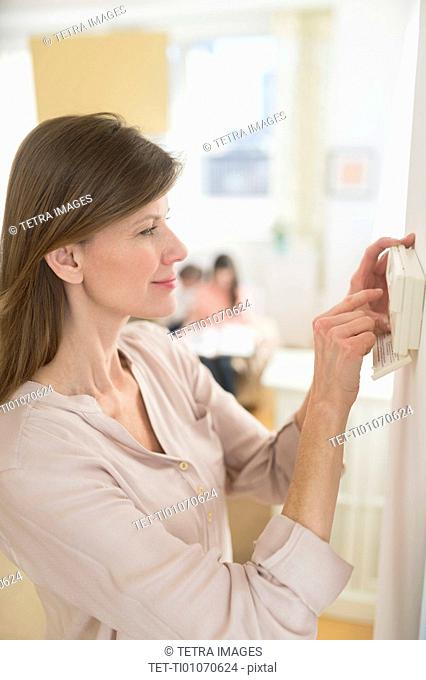 Woman adjusting house alarm
