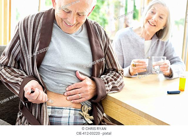 Older man giving himself injection