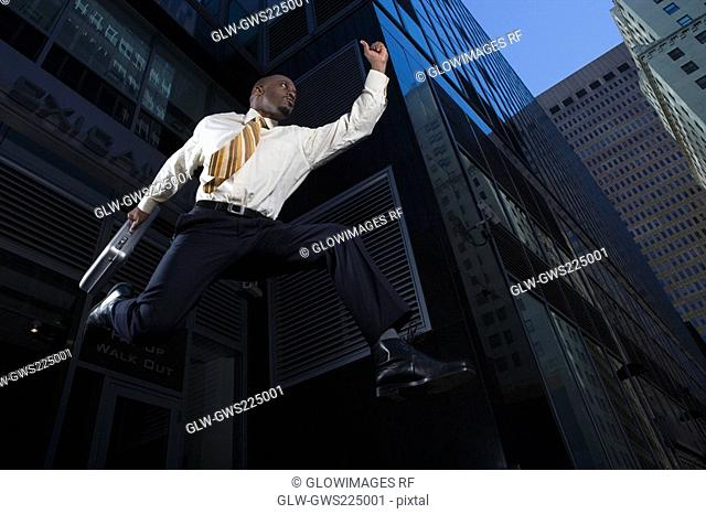 Low angle view of a businessman jumping with a briefcase