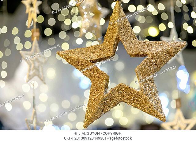Hanging golden star Christmas decoration on blurred background