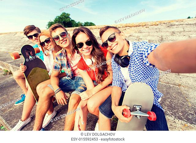 friendship, leisure, summer, technology and people concept - group of smiling friends with skateboard making selfie outdoors
