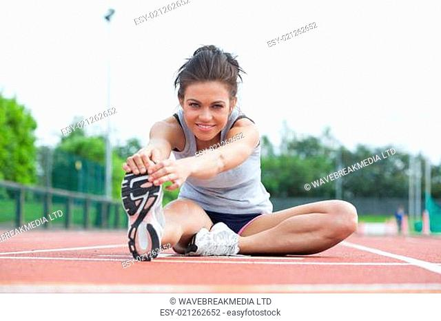 Woman stretching before race on track