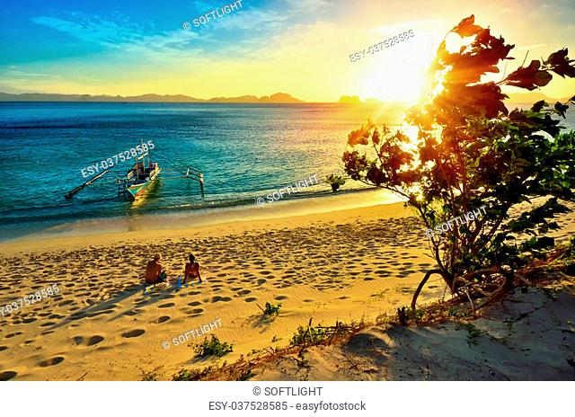 Young happy couple enjoying a beautiful sunset on the beach island of El Nido
