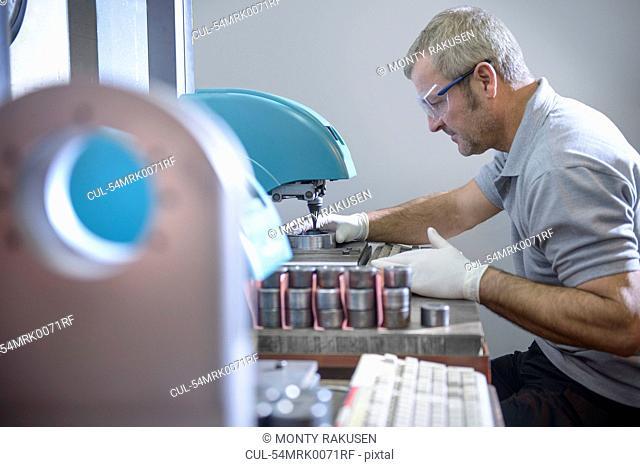 Engineer using polishing machinery