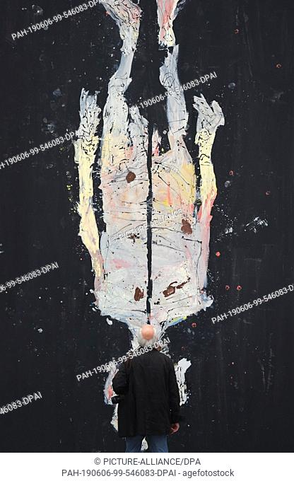 "06 June 2019, Bavaria, Munich: A visitor stands in front of the painting """"Avignon ade, 2017"""" by Georg Baselitz in the Pinakothek der Moderne"