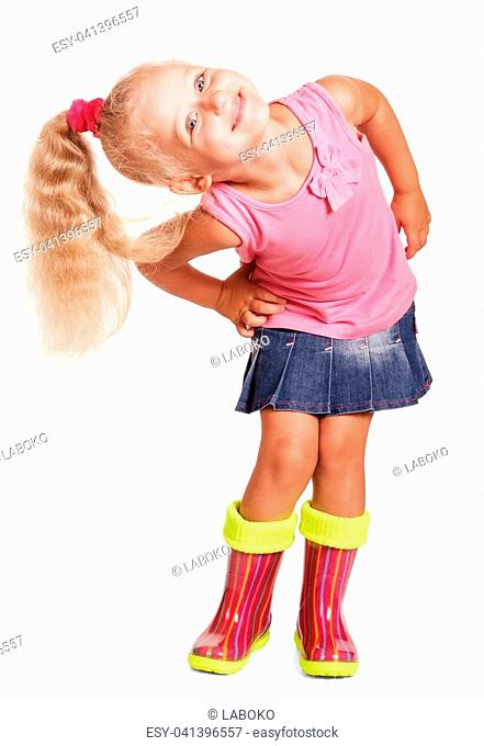 An impish little blond girl in a blouse, a skirt and rubber boots isolated on white background