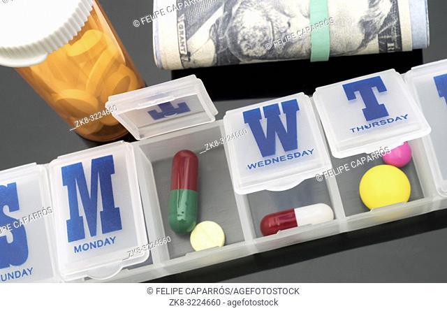 Pillbox next to banknotes of dollar, conceptual image