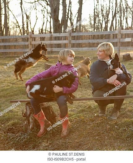 Mother and daughter outdoors, hugging goats and pet dog