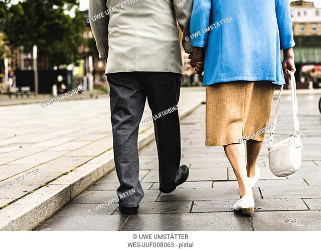 Back view of walking senior couple holding hands