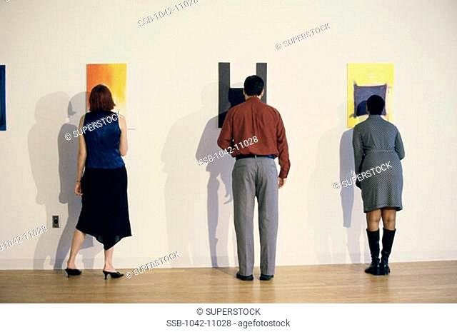 Rear view of a young man and two young women looking at paintings in a museum